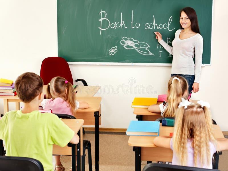 Nauczyciela writing przy blackboard w sala lekcyjnej zdjęcia royalty free