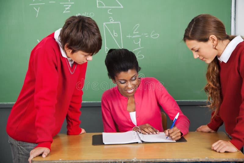 Nauczyciela Writing W segregatorze Podczas gdy uczni Stać obrazy royalty free