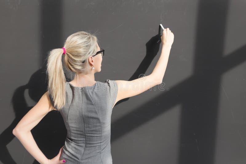 Nauczyciela writing z biel kredą na pustym blackboard w sala lekcyjnej obrazy royalty free