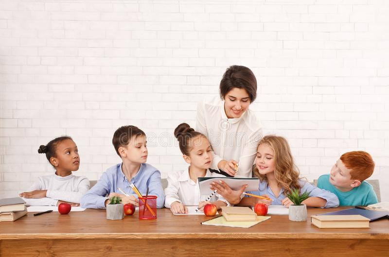 Nauczycieli pomaga dzieciaki pisze tescie w sali lekcyjnej zdjęcie stock
