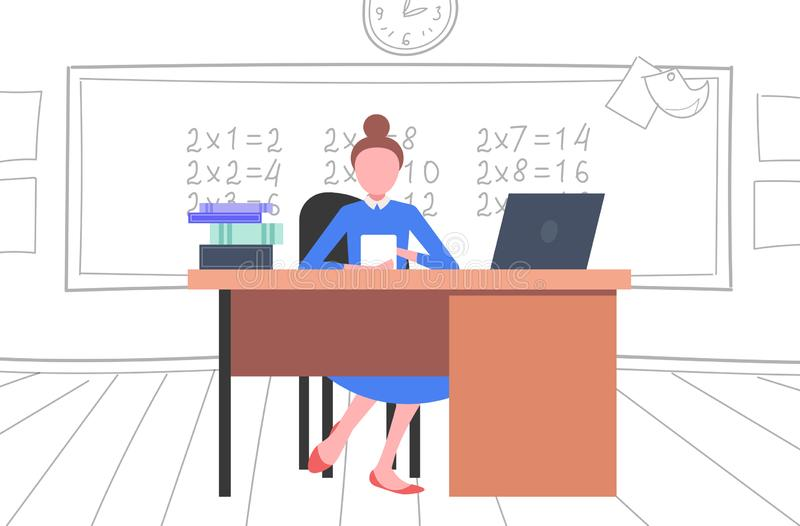 Nauczycielka siedząca przy biurku przy tablicy przy użyciu koncepcji nauczania matematyki laptopów w nowoczesnej szkole royalty ilustracja