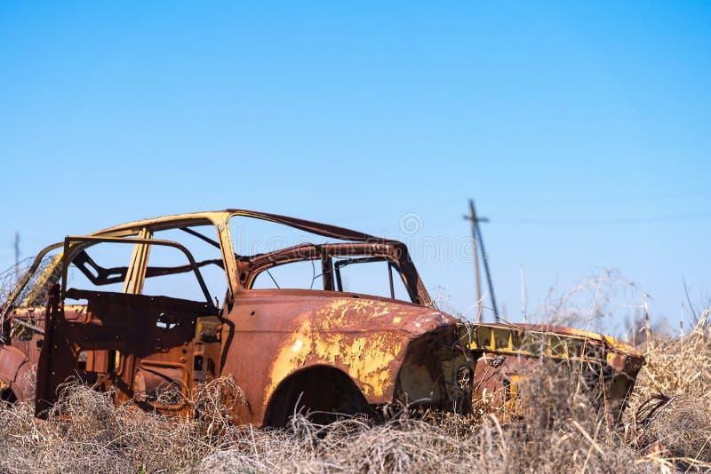 Naufrágio abandonado de um carro soviético amarelo do russo no meio do feno seco em Armênia do sul fotografia de stock royalty free
