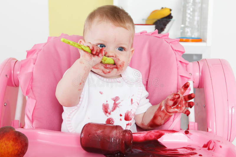 Naughty baby eating alone. In the high chair stock photography