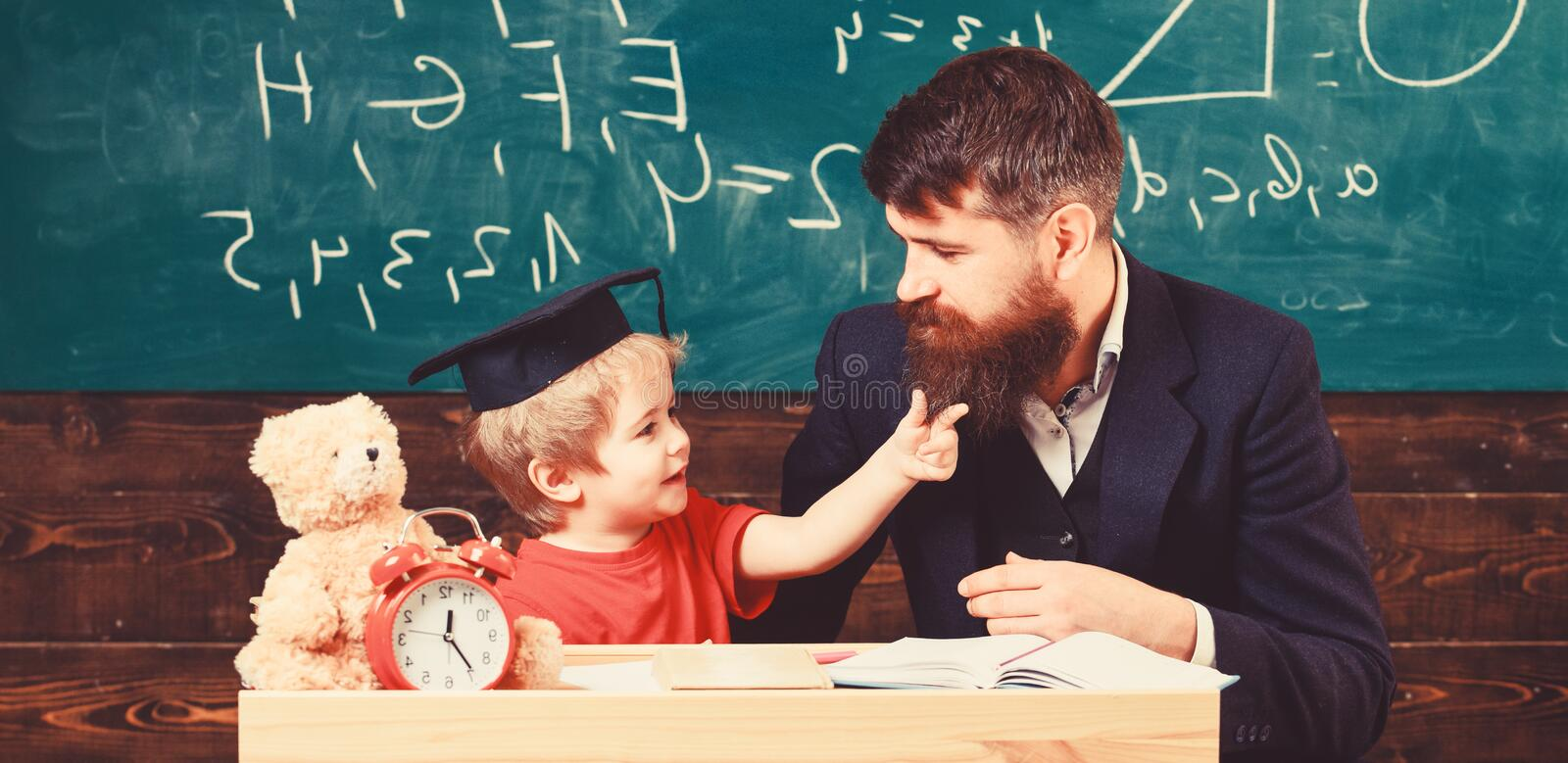 Naughty child concept. Father with beard, teacher teaches son, little boy. Kid cheerful distracting while studying royalty free stock image