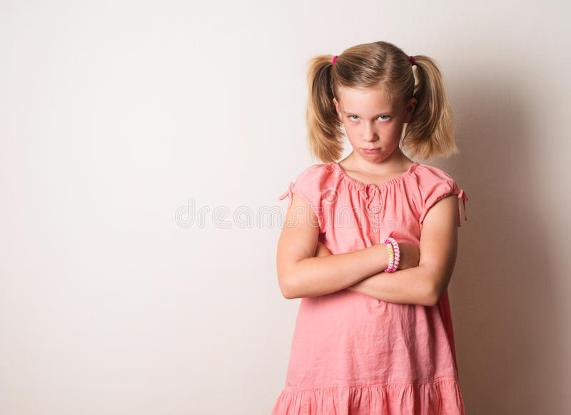 Naughty frowning girl with arms crossed. Sad, depressed, stressed, thoughtful girl. Human face expressions, emotions, feelings, r stock image