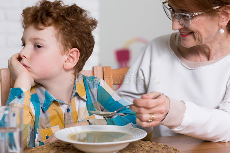 Naughty fussy eater and grandmother's dinner. Smiling grandmother feeding her grandson with soup. Little naughty fussy eater refusing to eat royalty free stock photos