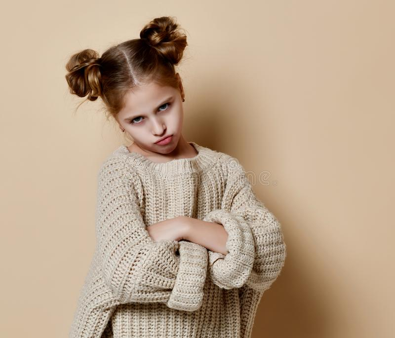 Naughty little girl over the beige background stock image
