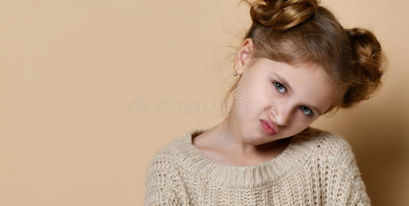 Naughty little girl over the beige background royalty free stock image