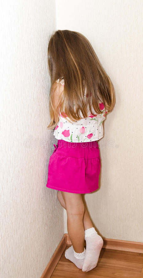 Naughty little girl is standing in the corner stock images