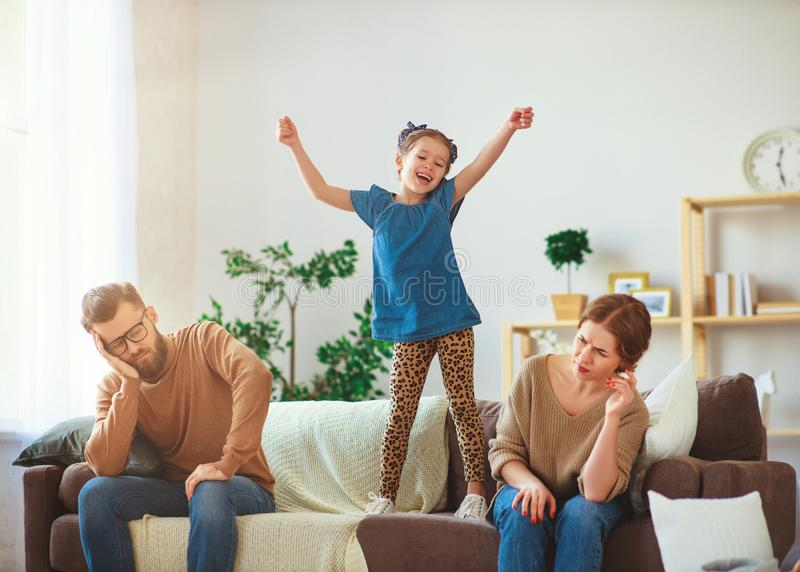 Naughty, mischievous, child girl jumping, laughing and having fun, parents stressed with  headache. Naughty, mischievous, child girl jumping, laughing and having royalty free stock images
