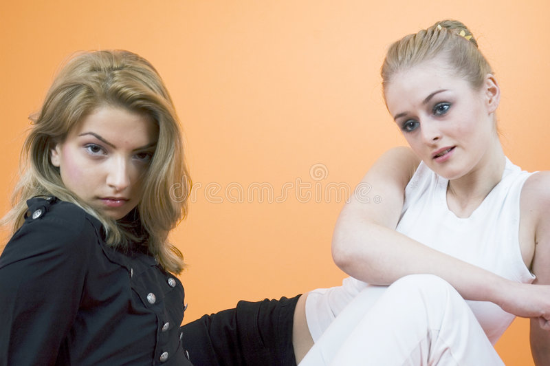 Naughty And Nice. Two young blond woman with opposite expressions. Taken in studio with an orange background stock photos