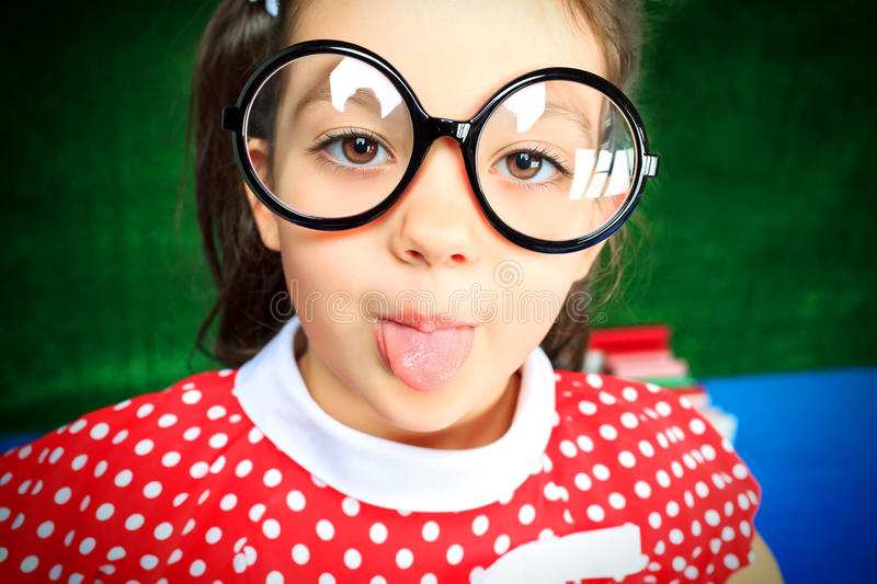 Naughty. Portrait of a funny little girl in big glasses stock image