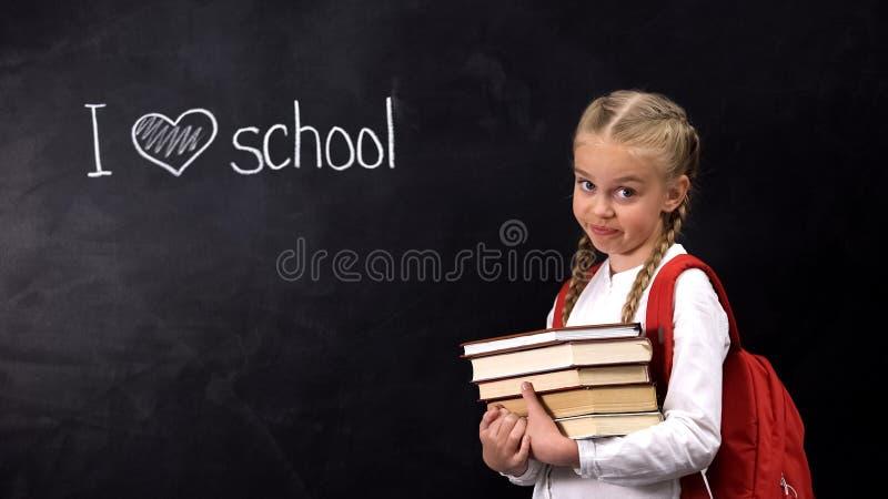 Naughty schoolgirl with books standing near blackboard, I love school phrase. Stock photo stock image
