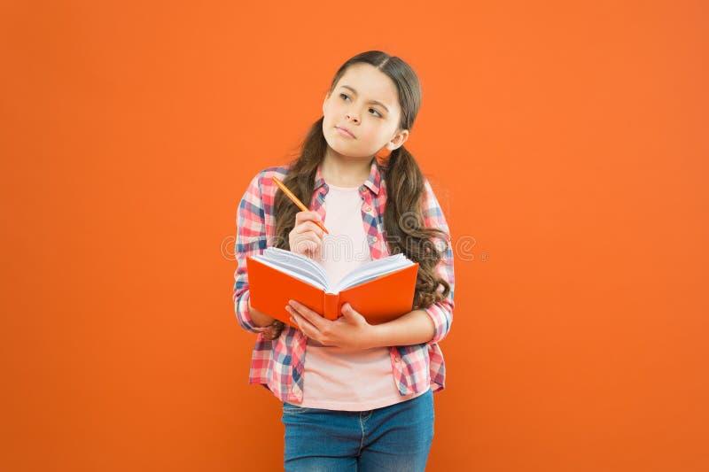 Nauka j?zyk Dziecko robi pracie domowej pisze w workbook Dziewczyna chwyta pi?ro i ksi??ka Dziewczyna ?liczna pisze puszka pomys? obraz royalty free