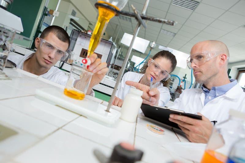 Nauka ucznie pracuje z substancjami chemicznymi w lab przy uniwersytetem obrazy stock