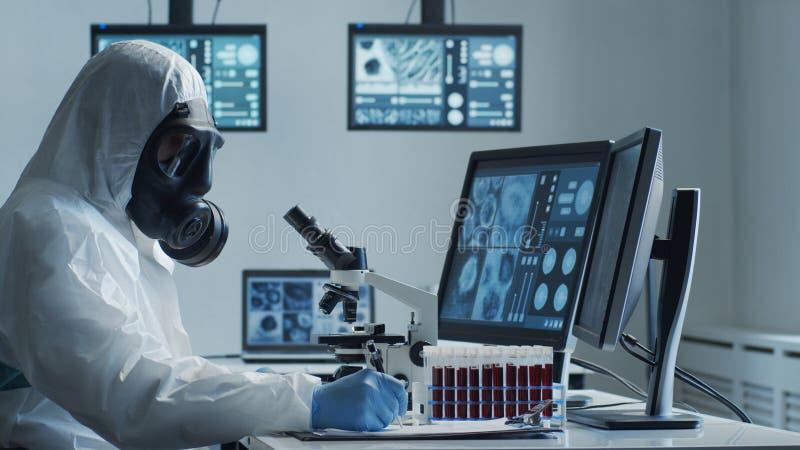Naukowcy zajmujący się kombinezonem ochronnym i maskami pracującymi w laboratorium badawczym przy użyciu sprzętu laboratoryjnego: fotografia royalty free