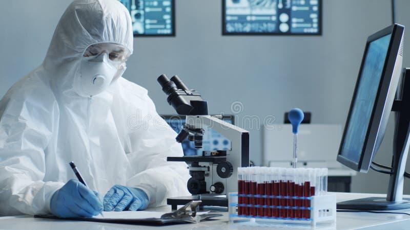 Naukowcy zajmujący się kombinezonem ochronnym i maskami pracującymi w laboratorium badawczym przy użyciu sprzętu laboratoryjnego: zdjęcia stock