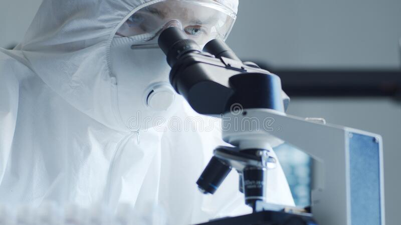 Naukowcy zajmujący się kombinezonem ochronnym i maskami pracującymi w laboratorium badawczym przy użyciu sprzętu laboratoryjnego: obraz stock