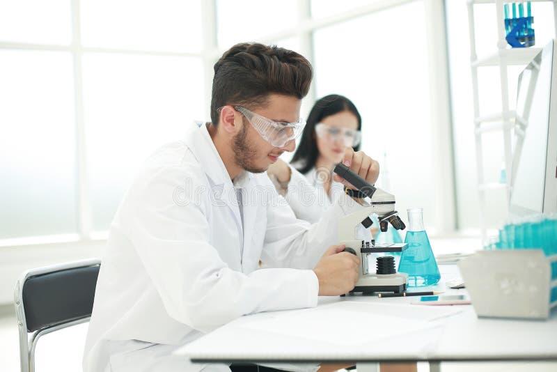 Naukowiec biolo?ki siedzi przy laboratorium sto?em obrazy royalty free