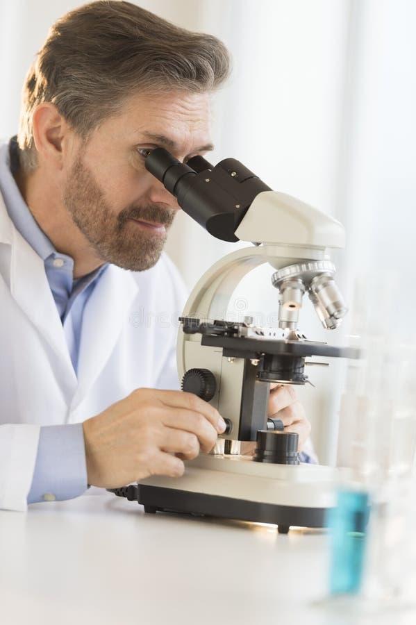 Naukowiec Patrzeje Przez mikroskopu obraz royalty free