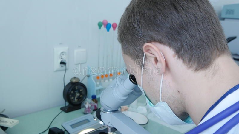 Naukowiec pracuje z mikroskopem obrazy stock