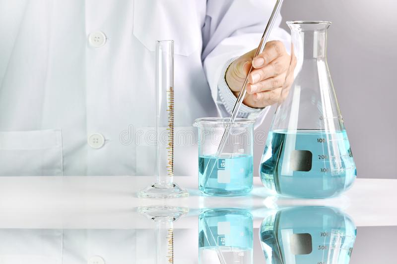Naukowowie bada w laboratorium, chemik trzyma naukowego glassware wyposażenie zdjęcia stock
