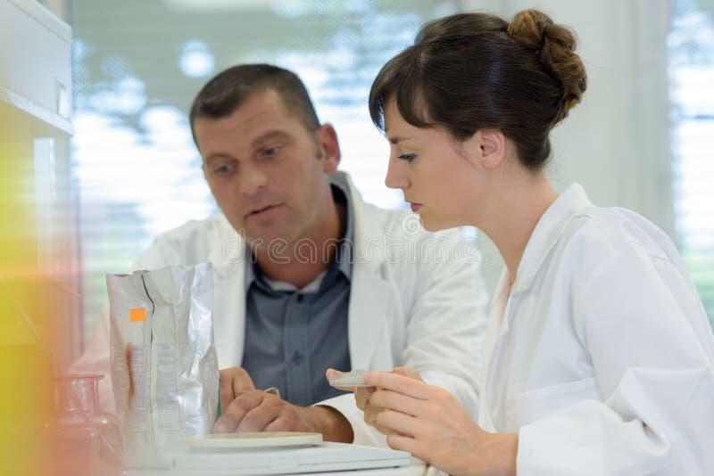 Naukowowie egzamininuje w lab z próbnymi tubkami obraz royalty free