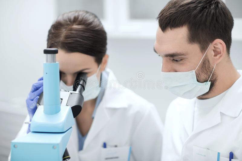 Naukowowie patrzeje mikroskop przy lab w maskach obrazy stock