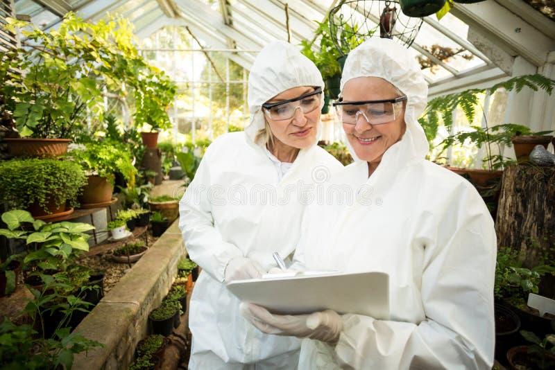 Naukowowie patrzeje schowek w czystym kostiumu podczas gdy egzamininujący roślinę zdjęcia stock