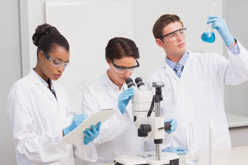 Naukowowie pracuje attentively z mikroskopem i zlewką obraz stock