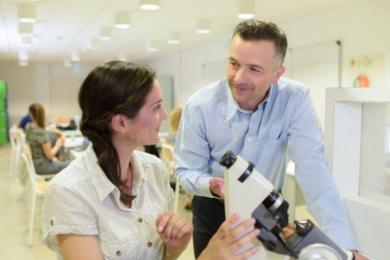 Naukowowie w dyskusji micrscope w lab zdjęcia stock