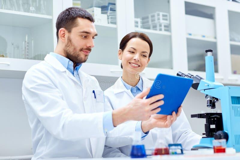 Naukowowie z pastylka komputerem osobistym i mikroskop w lab obraz stock