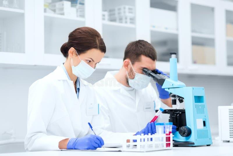 Naukowowie z schowkiem i mikroskopem w lab zdjęcie royalty free