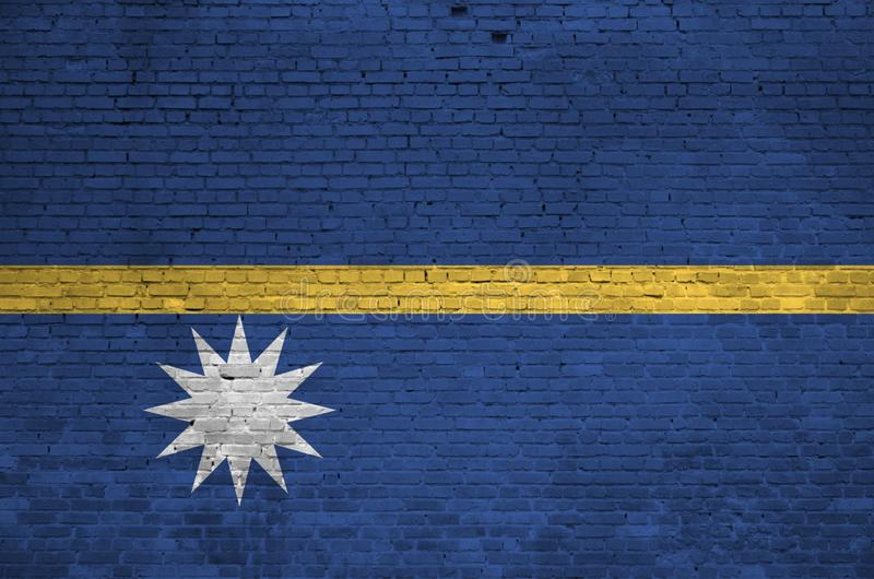 Nauru flag depicted in paint colors on old brick wall. Textured banner on big brick wall masonry background. Nauru flag depicted in paint colors on old brick royalty free stock photography