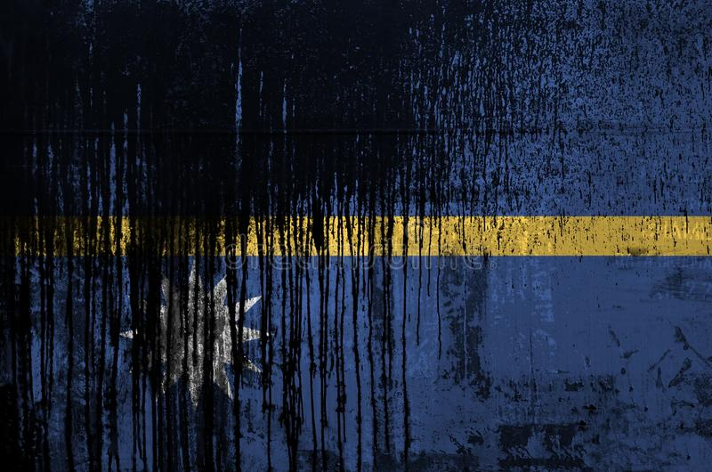 Nauru flag depicted in paint colors on old and dirty oil barrel wall closeup. Textured banner on rough background. Nauru flag depicted in paint colors on old and stock photos