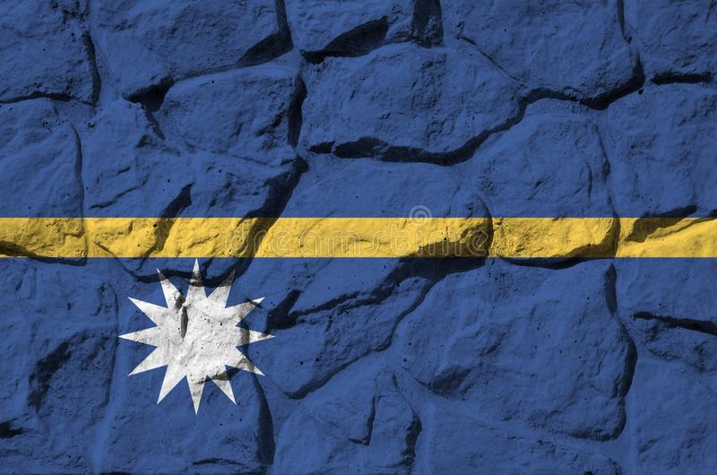 Nauru flag depicted in paint colors on old stone wall closeup. Textured banner on rock wall background. Nauru flag depicted in paint colors on old stone wall royalty free stock photo