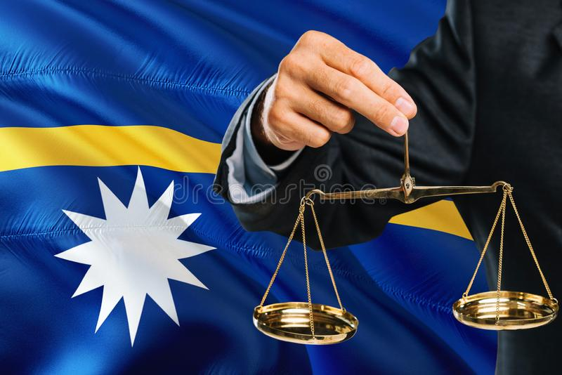 Nauruan Judge is holding golden scales of justice with Nauru waving flag background. Equality theme and legal concept vector illustration