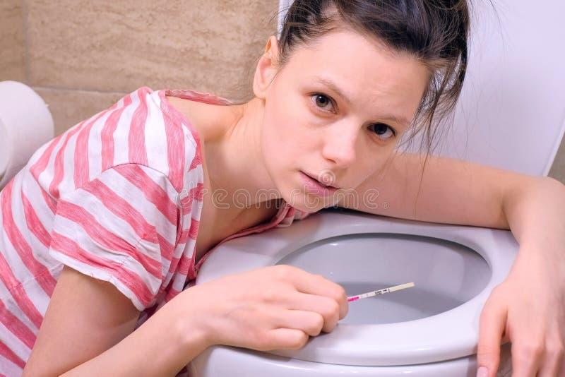 Naus?e matinale La jeune femme fatiguée enceinte vomit dans le lookin de toilette à la maison à la caméra photos libres de droits