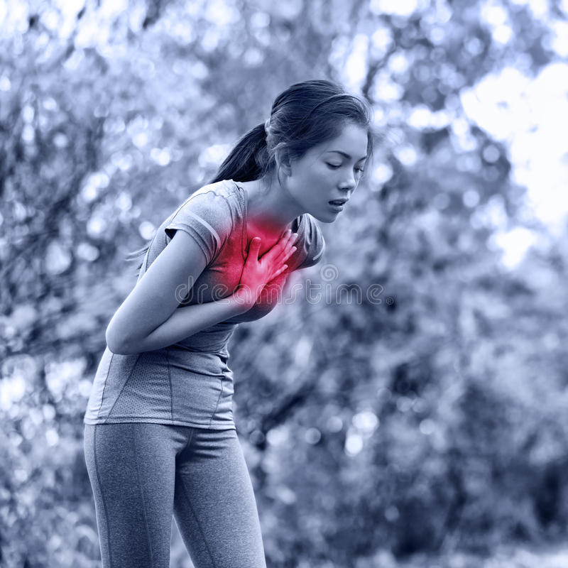 Nausea - nauseous and sick ill runner vomiting. Running woman feeling bad about to throw up. Girl having nausea from dehydration or chest pain stock photo