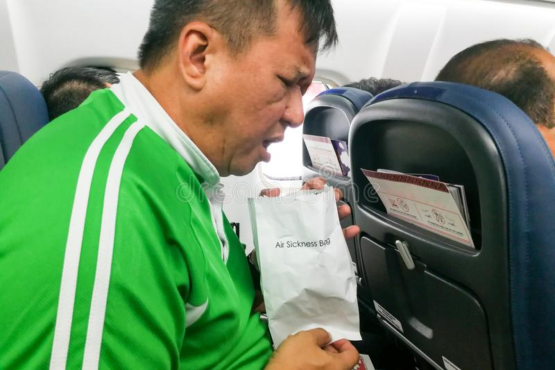 Nauseous air sickness Asian man vomiting into air sickness bag. In cabin stock image