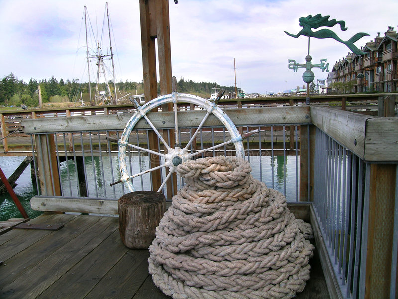 Nautical. Coil of nautical rope, boat steering wheel , weather vane on dock royalty free stock photography