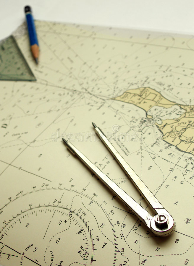 Nautical chart and dividers. A blue wood pencil pointing to a place on an old nautical chart, used for sailing and navigation on seas and oceans. Topographical royalty free stock image