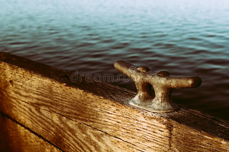 Nautical Cleat. On pier closeup with water background royalty free stock image