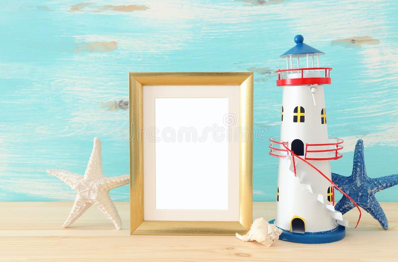 Nautical concept with empty photo frame and lighthouse over wooden table. For photography montage royalty free stock images