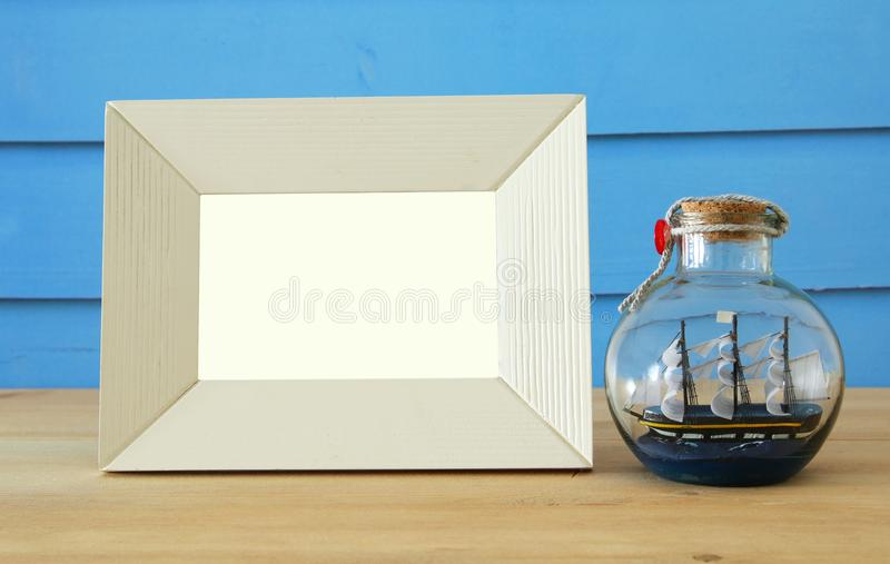 Nautical concept with empty photo frame and sail boat in the bottle over wooden table. For photography montage. stock images