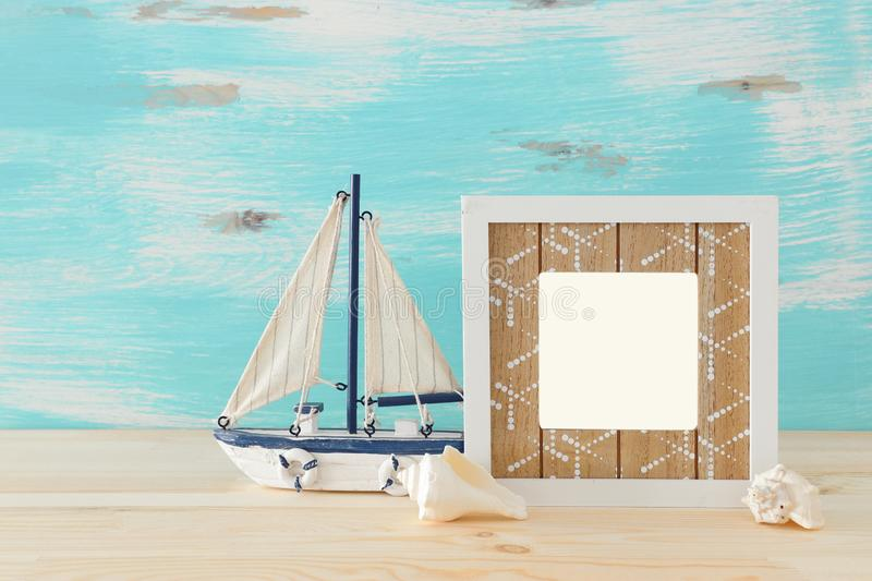 Nautical concept with empty photo frame and sail boat over wooden table. For photography montage stock image