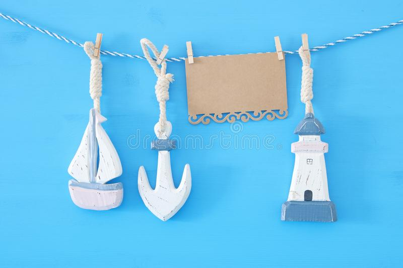 nautical concept with sea lifestyle decorations: sail boat and anchor hanging on a string over blue wooden background. royalty free stock photo