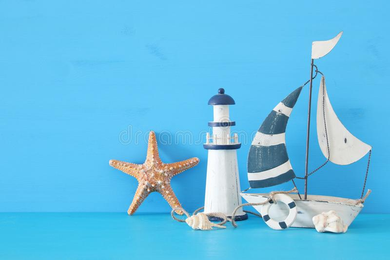 nautical concept with white decorative sail boat, lighthouse, starfish, seashells over blue wooden table and background. royalty free stock photo