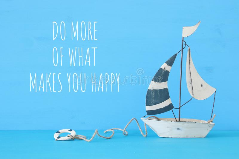 Nautical concept with white decorative sail boat over blue wooden table and text: Do more of what makes you happy. Nautical concept with white decorative sail stock photos
