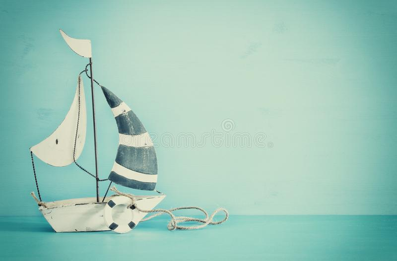 nautical concept with white decorative sail boat over blue wooden table. Vintage filtered image. stock photo
